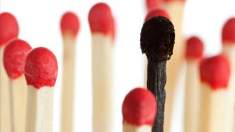 burnt match between new matchsticks, shallow depth of field